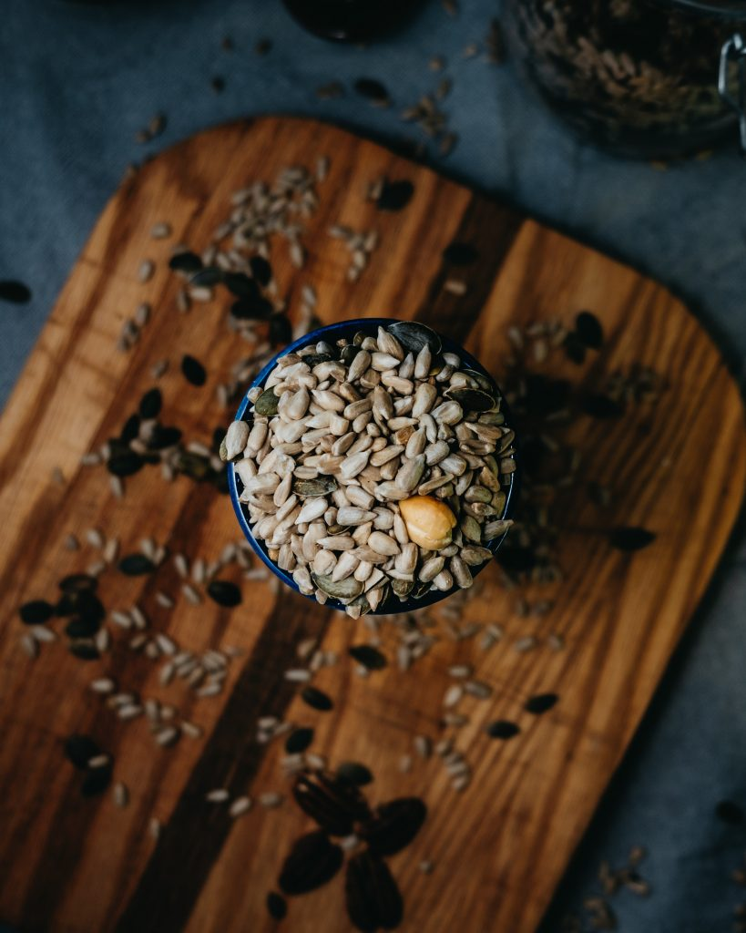Image of a bowl containing nuts and seeds.  Nuts and seeds are great whole food magnesium sources and can help boost magnesium levels to combat stress.